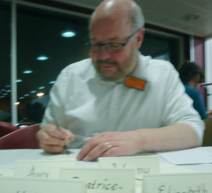 Jonathan writing out place cards at Sainsbury's.